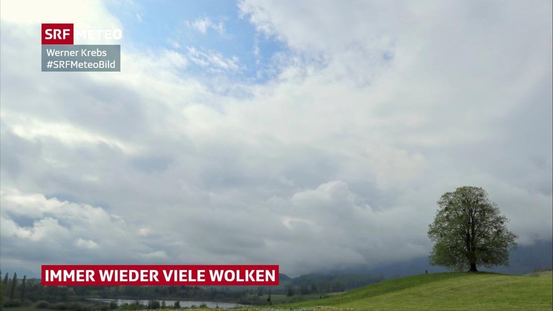 Bild beinhaltet viele Wolken, aber auch Wolkenlücken mit Sonnenschein.