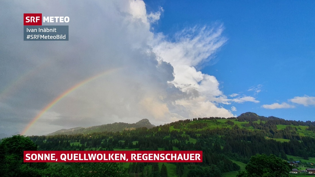 Cumuluswolke mit Regenbogen neben blauem Himmel.