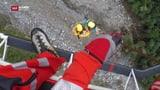 Am Seil hängend bohren die Spezialisten am Hang (Artikel enthält Video)