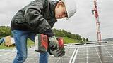 Ein Junge mit Helm und einer Bohrmaschine befestigt Solarzellen.