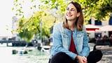 Eine junge Frau sitzt an einer Flusspromenade und trägt eine Jeans-Jacke.