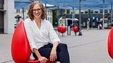Eine junge Frau sitzt auf einem roten Sessel auf einem Bahnhofsplatz.