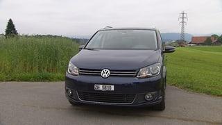 Dunkelblauer VW-Van steht auf einer Nebenstrasse.