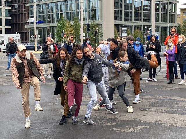 Mitglieder des Ballett-Ensembles tanzen auf dem Bahnhofsplatz