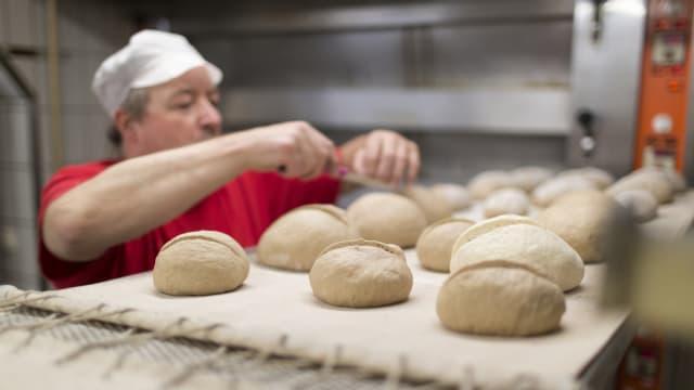 Ein Bäcker legt Brote auf das Blech.