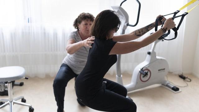 Eine Physiotherapeutin korrigiert die Übung einer Patientin.