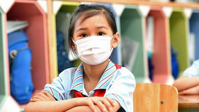 Kind mit Mund-Nasen-Schutz.