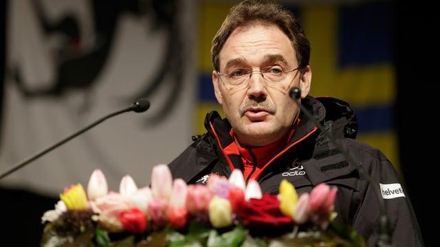Mann vor Mikrofon und Blumen