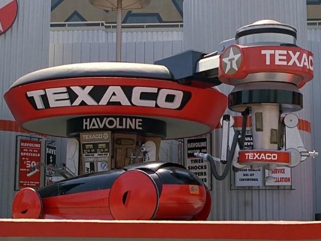 Futuristisches Auto an einer vollautomatischen Zapfsäule; gross angeschrieben mit «Texaco».