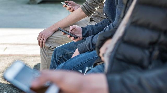 Junge Menschen sitzen und beschäftigen sich mit Handy.