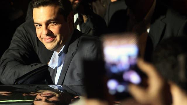 Tsipras wird mit Handys fotografiert und steigt in ein Auto, ein Lächeln auf dem Gesicht.