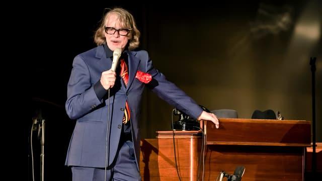 Mann in Anzug steht auf einer Bühne. Mit der einen Hand lehnt er sich an ein Klavier, mit der anderen hält er ein Mikrofon