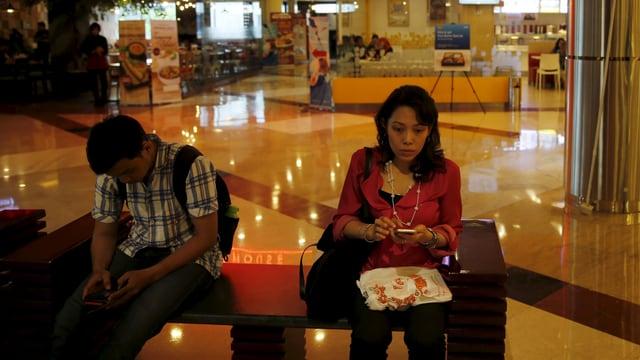 Zwei Menschen sitzen mit ihren Smartphones auf einer Bank in einem Shoppingcenter
