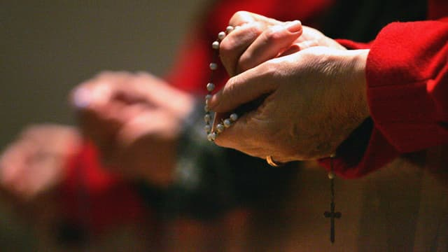 Eine Gläubige betet in der Dreifaltigkeitskirche in Bern den Rosenkranz.