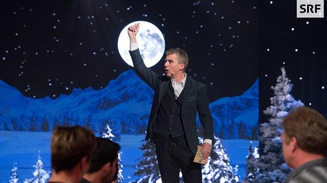 Reto Scherrer vor der Bühnen-Kulisse. Blau beleuchtete Berge und ein voller, leuchtender Mond - davor hält Reto Scherrer seine Hand hoch.