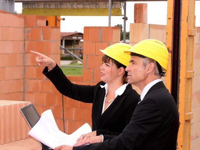 Architektin und Polier auf einer Baustelle mit Bauplan in der Hand.