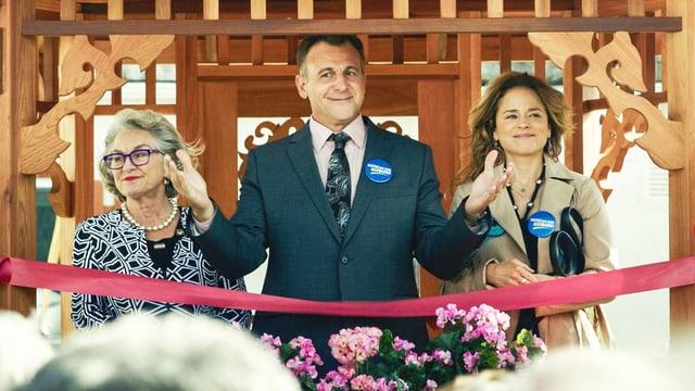 Ein Mann im Anzug und zwei Frauen. Der Mann scheint auf Wahlkampf zu sein.