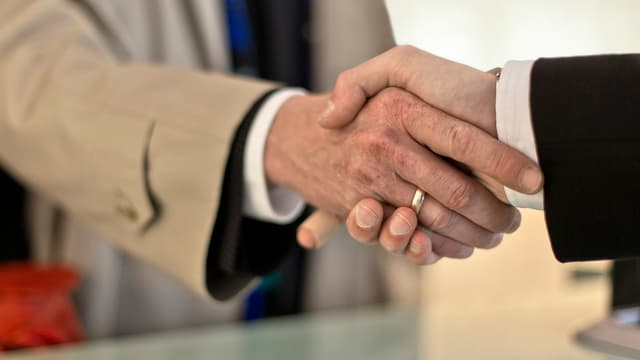 Ein Bankangestellter und ein Kunde reichen sich an einem Bankschalter die Hände. (Keystone/Symbolbild)