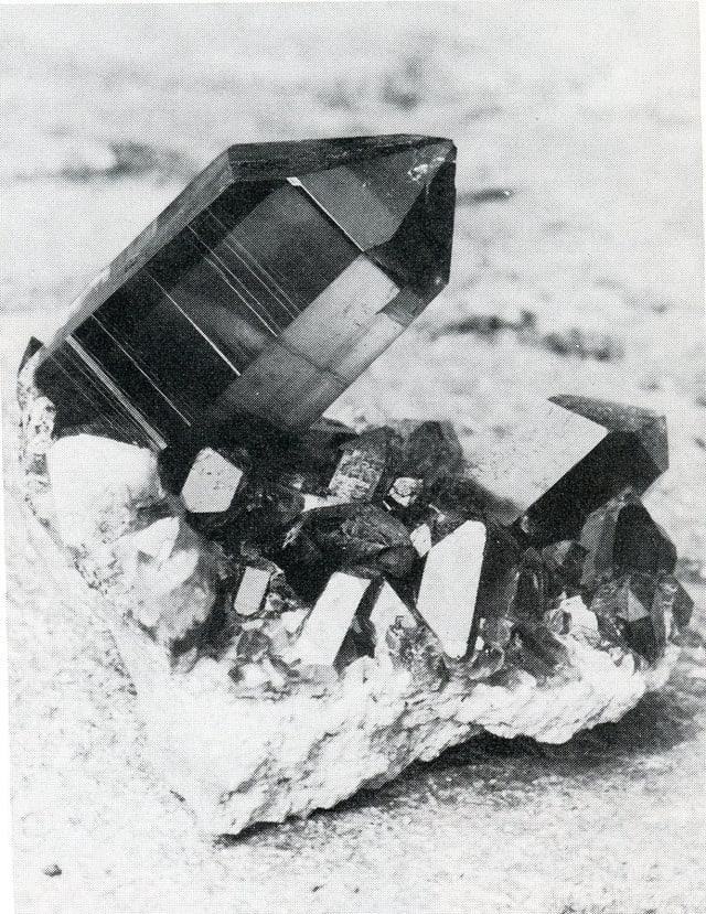 Cristallas nairas (quarz) cun adulars