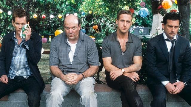 Drei Männer sitzen in einem Park. Im hintergrund sind Lampions erkennbar.