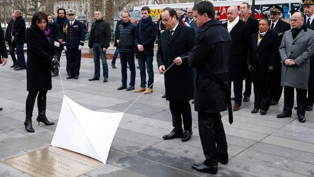 Il president François Hollande, il primminister Manuel Valls e la burgamestra da Paris Anne Hidalgo svelan la tavla commemorativa.