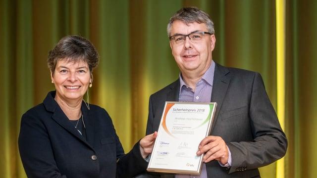 Ein Mann im Anzug zeigt eine Urkunde. Er erhält sie von bfu-Direktorin Brigitte Buhmann, die ihm die Hand schüttelt.