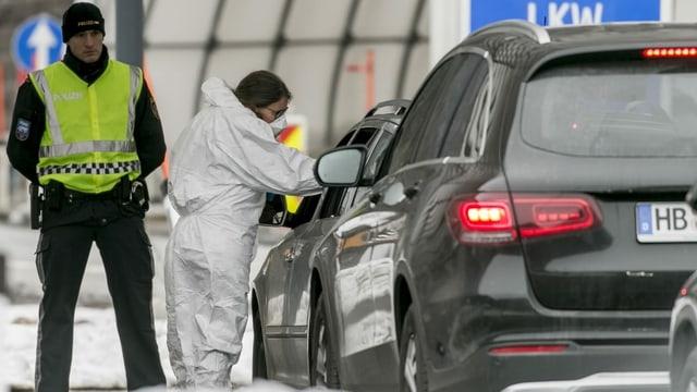 Eine Ärztin kontrolliert die Temperatur eines Autofahrers an einem Grenzübergang.