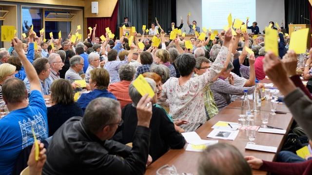 Die Teilnehmenden an der Gemeindeversammlung in Kandersteg heben ihr Stimmkärtchen. Sie heissen damit einen Kredit für Olympische Winterspiele 2026 in der Schweiz gut.