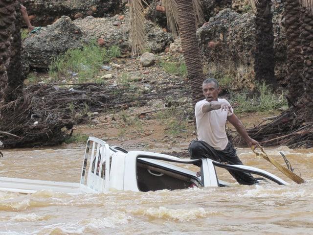 Ein Mann in Kleidern sitzt auf einem kaputen Autodach. Das Auto bis zu den Scheiben in den Fluten.
