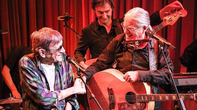 Zwei Männer reichen sich die Hand auf der Bühne bei einem Konzert. Einer hat eine Gitarre umhängen.
