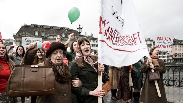 Frauen demonstrierend auf einerr Brücke.