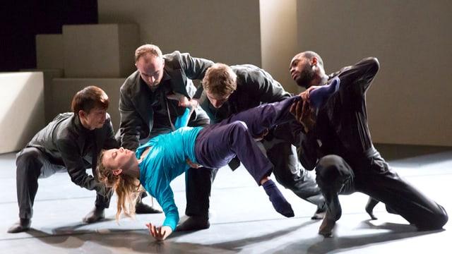 Vier Tänzer tragen eine Frau.