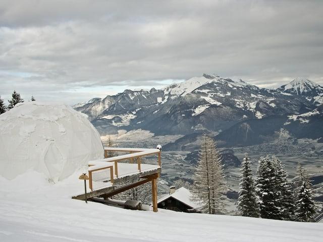 Verschneites, kugelförmiges Zelt mit Blick ins Tal und die Berge.