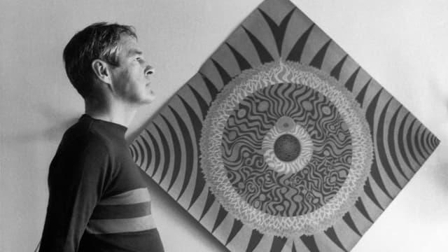 ein schwarz-weiss Foto eines Mannes, der vor einem Mandala steht