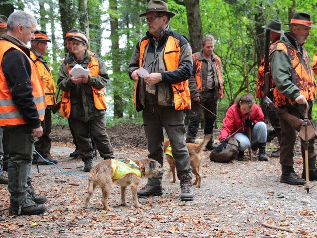 Jäger stehen in Leuchtwesten im Wald, bereit zum Abmarsch.