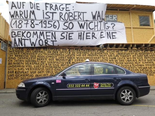 Taxi vor der Spanplattenwand mit Texten von Walser