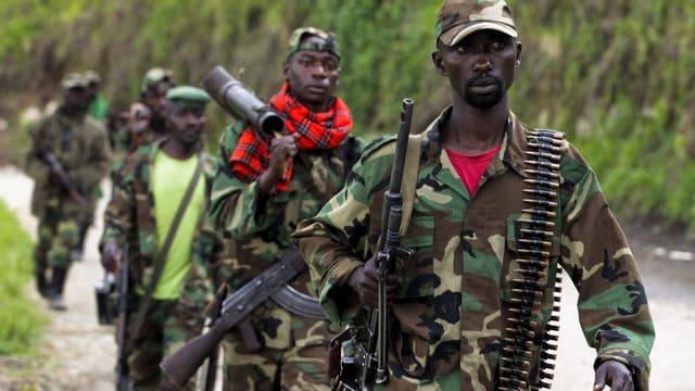 Schwerbewaffnete Männer in Kampfanzügen.