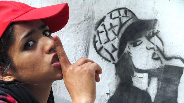 Eine Frau mit Baseballcap macht mit dem Zeigefinger eine «Pssst»-Geste, an der Wand hinter ihr macht eine gesprayte Frau dasselbe.