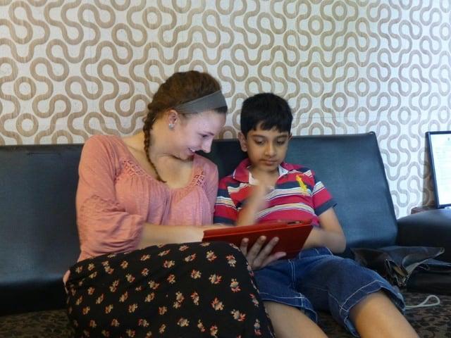 Eine junge Amerikanerin zeigt einem autistischen indischen Kind etwas auf einem iPad.