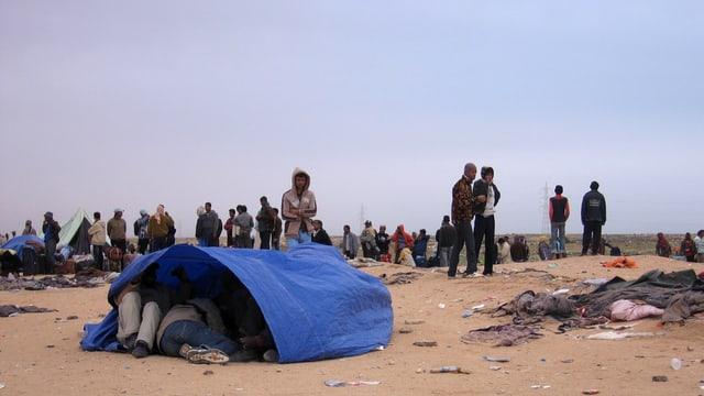 Flüchtlinge in der Wüste, im Vordergrund ein blaues Zelt, in dem Menschen liegen.