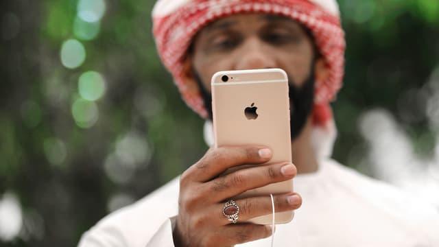 Symbolbild: Ein Mann mit Turban schaut auf sein Smartphone.
