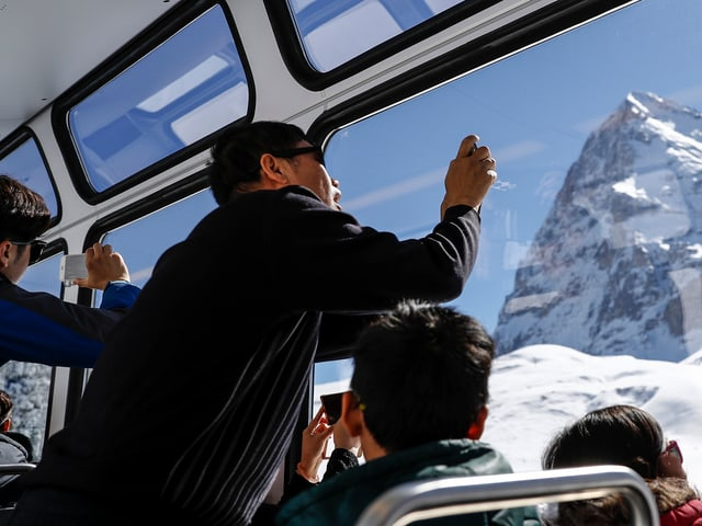 Chinesische Touristen machen Fotos von der Eigernordwand.