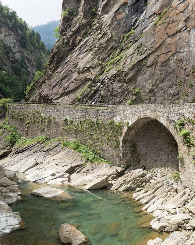 Eine Brücke an einem steilen Fels.