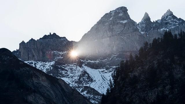 Ein Loch in einer Bergkette, das sogenannte Martinsloch. Durchs Loch scheint die Sonne.