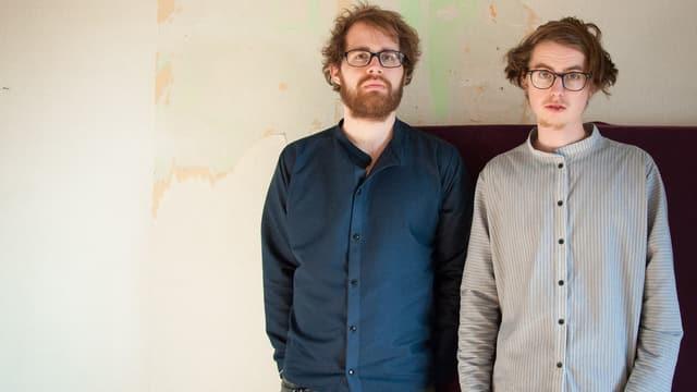 zwei bärtige und brillentragende hipster gucken desinteressiert in die kamera
