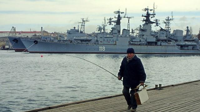 Ein Mann läuft am Quai, im Hintergrund ein Kriegsschiff.