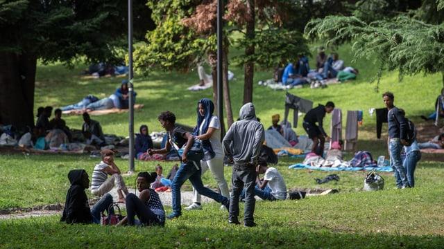 Purtret da fugitivs che giaschan u sesan en in parc a Como.