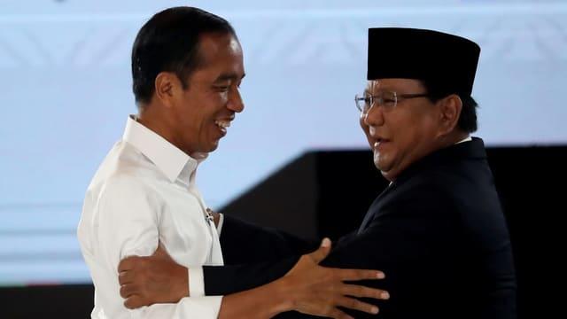 Joko Widodo und Prabowo Subianto halten sich an den Armen fest.