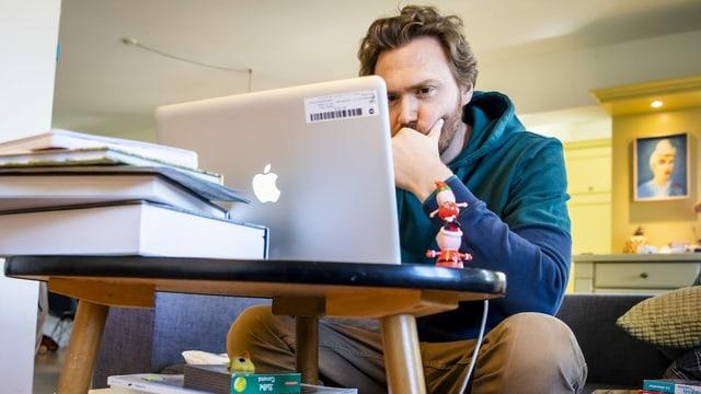 Ein Mann arbeitet daheim auf seinem Sofa am Computer