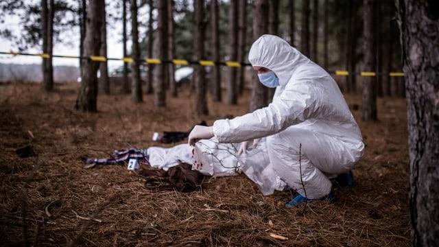 ein Kriminalbeamter in Onverall begutachtet eine Leiche im Wald